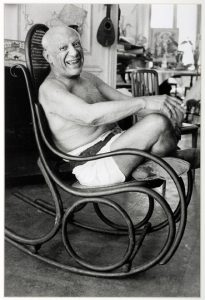 Picasso laughing in his favorite rocking chair 1957